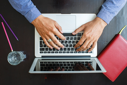 Cropped image of a young man working on his laptop